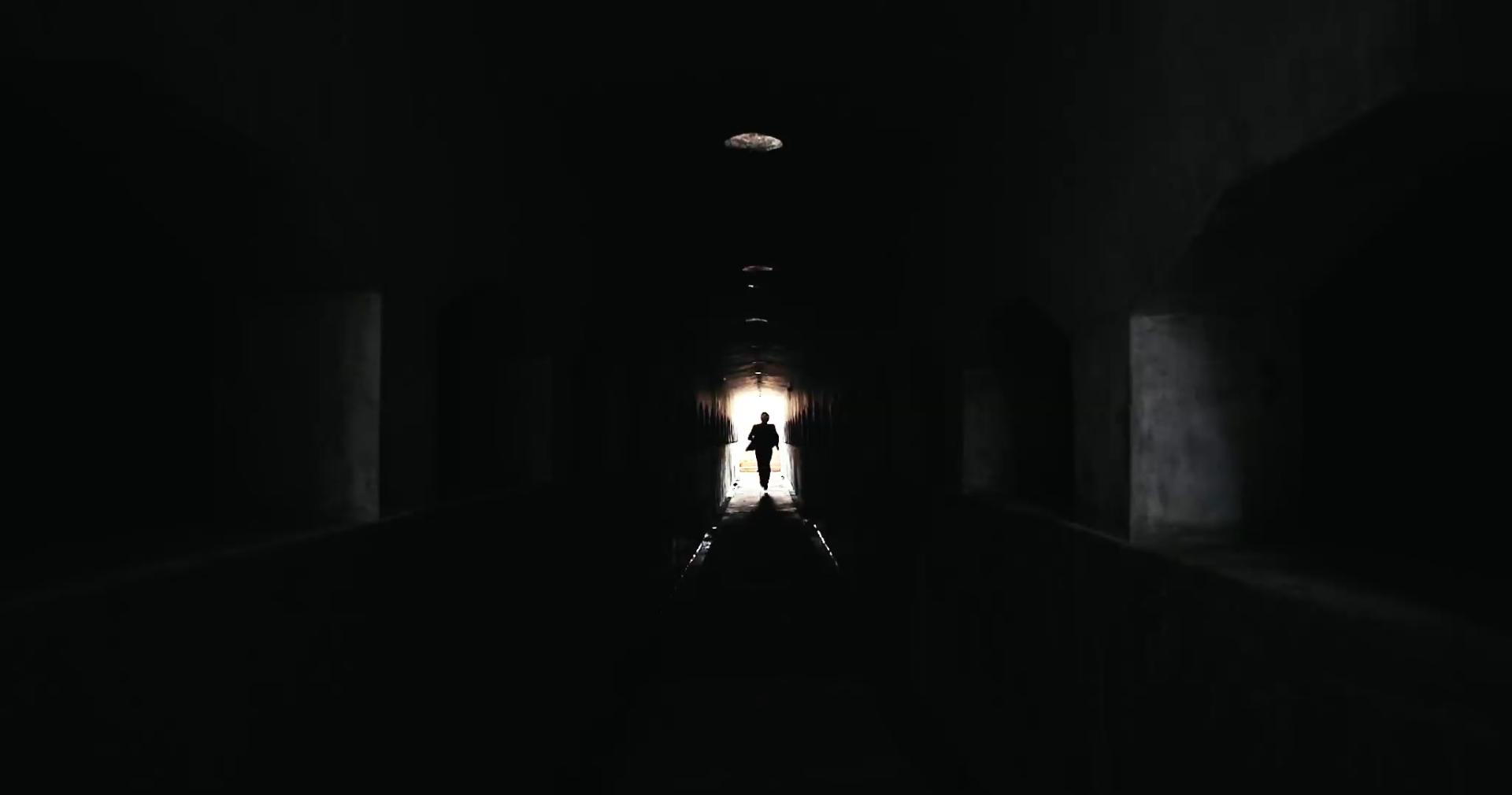 K. rennt durch einen dunklen Durchgang
